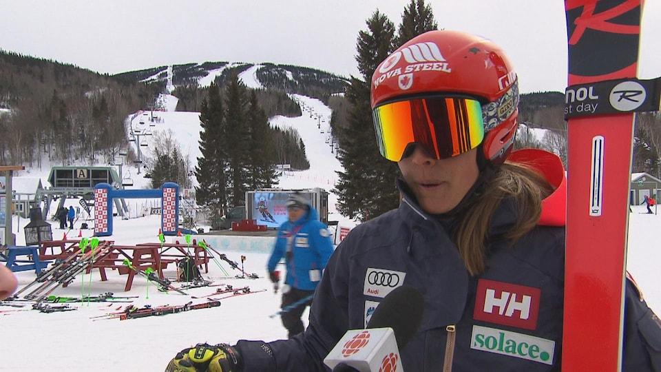 Avec son casque, ses lunettes et ses skis sur l'épaule, elle donne une entrevue à Radio-Canada.
