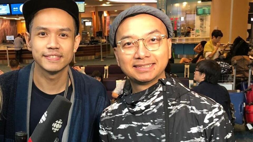 Les deux hommes sourient à la caméra. L'un porte une casquette, l'autre un chapeau.