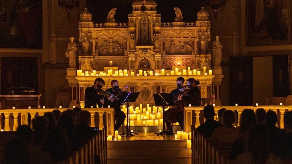 Performance d'un quatuor à cordes, éclairé par des chandelles, dans la chapelle Notre-Dame-de-Bon-Secours à Montréal.