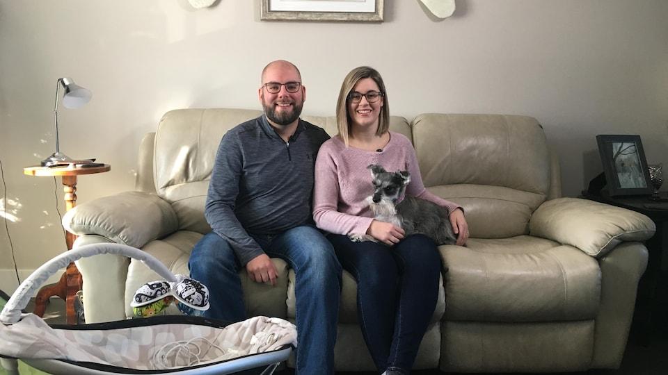Un homme et une femme avec un chien sur les genoux sont assis sur un sofa.