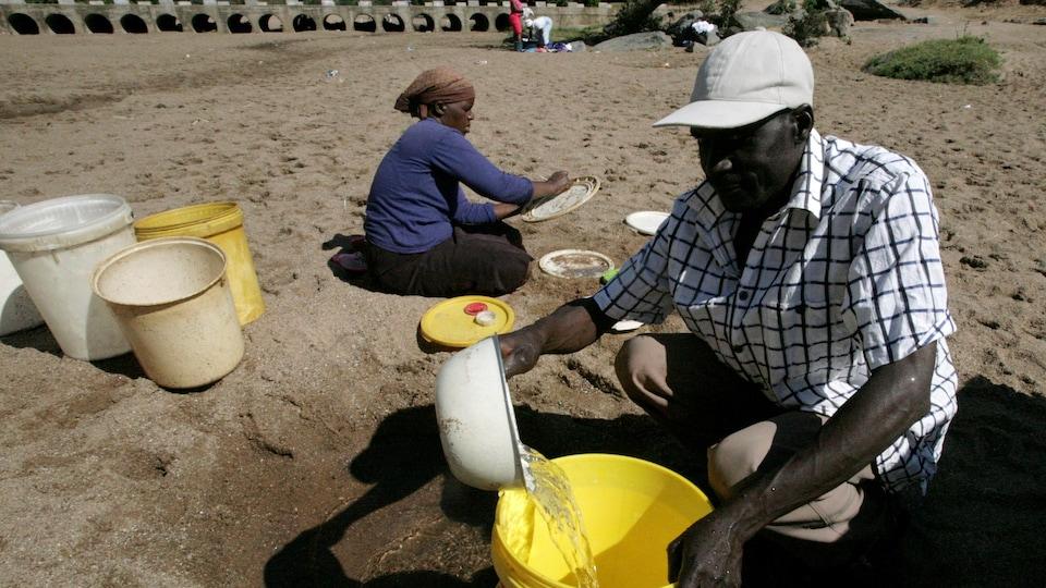 Des villageois recueillent l'eau d'une rivière asséchée, lors de la sécheresse qui a frappé le Zimbabwe.