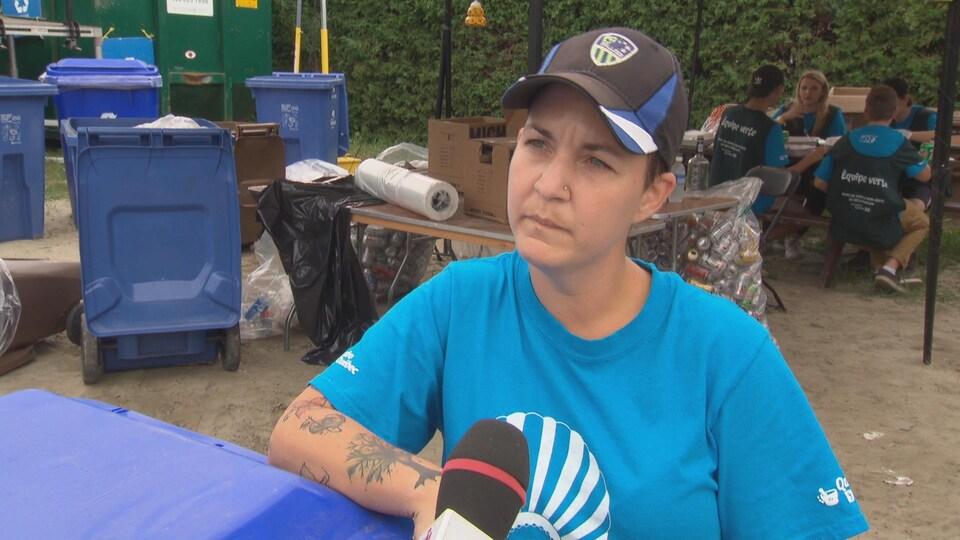 Une femme avec une casquette s'appuie sur un bac de recyclage lors d'une entrevue à al caméra de Radio-Canada.