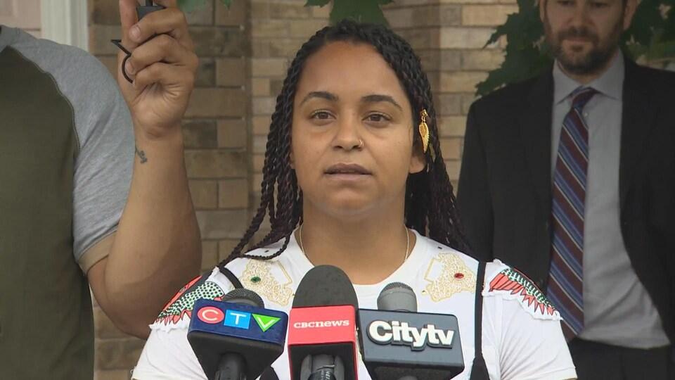 Une femme noire, devant des micros de médias, à l'extérieur.