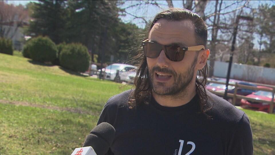 Un homme avec une barbe et des lunettes fumées parle au micro.