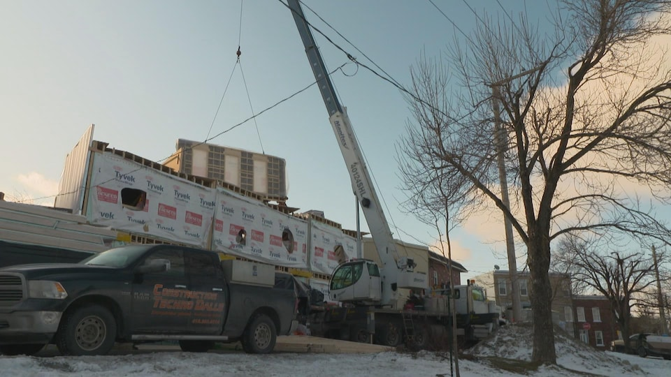 Un chantier de construction avec une camionnette à l'avant et une grue à l'arrière.