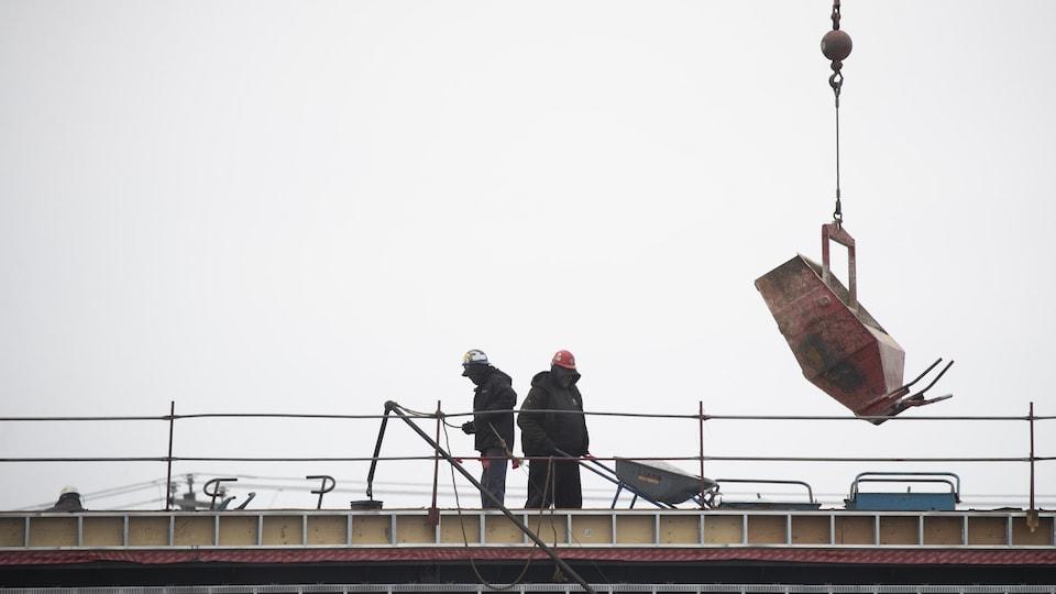 Deux ouvriers travaillent côte à côte sur un chantier.