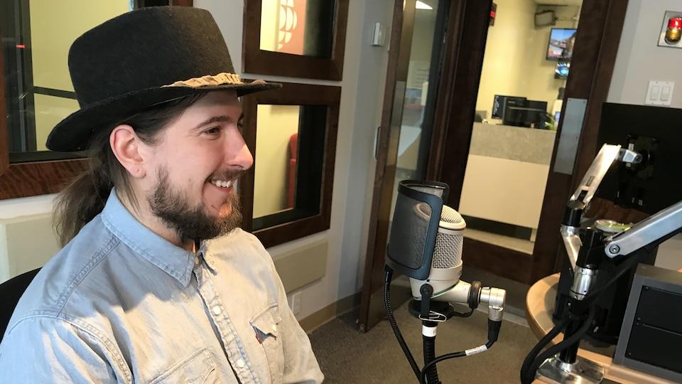 Un homme portant un chapeau de feutre sourit dans nos studios de Rouyn-Noranda.