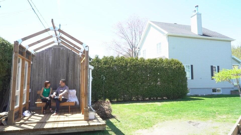 Un couple assis sur un banc, sous une charpente de chapelle en construction.