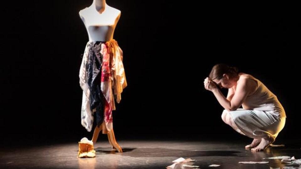 Une femme est accroupie, la tête dans ses mains, devant un mannequin de couture.