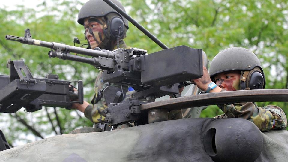 Deux soldats taïwanais en position sur un char d'assaut de fabrication américaine lors d'un entraînement militaire.