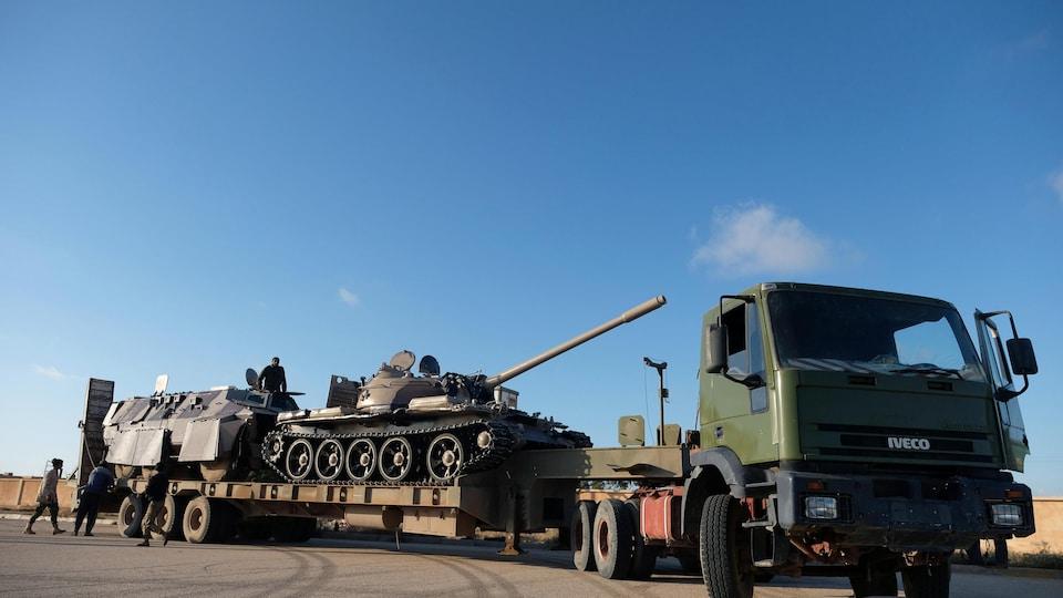 Un char d'assaut sur une remorque tirée par un camion.