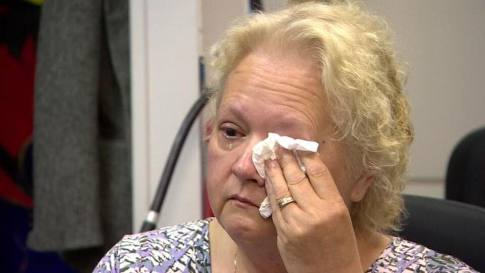 Charlene Klyne sèche ses larmes à l'aide d'un mouchoir.