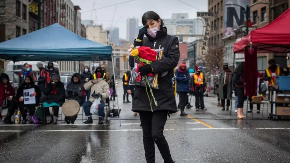 Charlene Brunelle devant d'autres manifestants masqués.