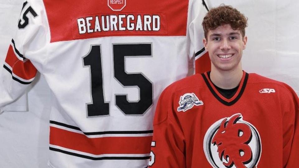 Charles-Antoine Beauregard sourit à côté de son chandail de hockey accroché sur un mur.