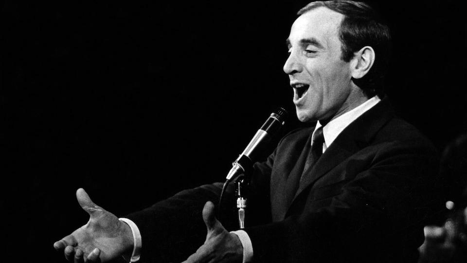 Le chanteur français Charles Aznavour chante, les bras ouverts et un micro sur pied devant lui.