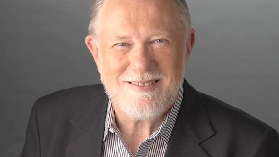 Portrait d'un homme avec une barbe blanche et portant un veston noir.