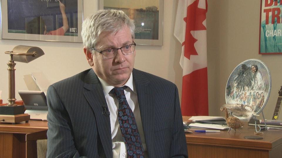 Charlie Angus est assis dans un bureau, alors qu'on aperçoit un drapeau canadien en arrière-plan.