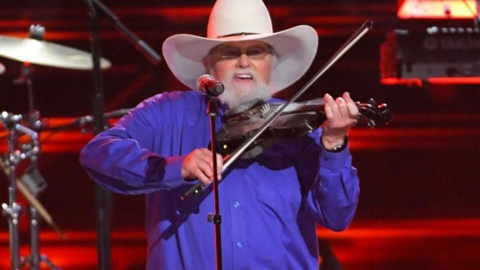 Le musicien joue du violon sur scène.