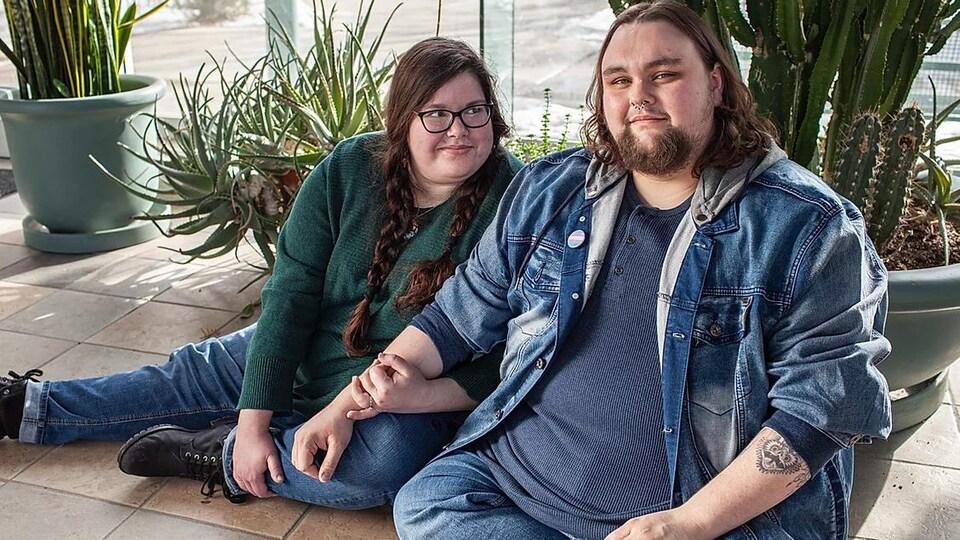 Deux personnes sont assises ensemble sur le sol, avec diverses plantes en pot en arrière-plan.