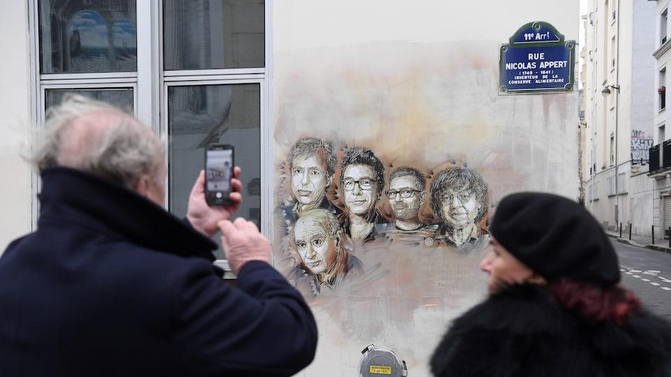 Un passant prenant en photo le graffiti représentant les visages des journalistes de Charlie Hebdo.