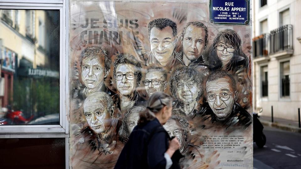 Une femme passe devant une murale reproduisant les visages de 10 employés de Charlie Hebdo.