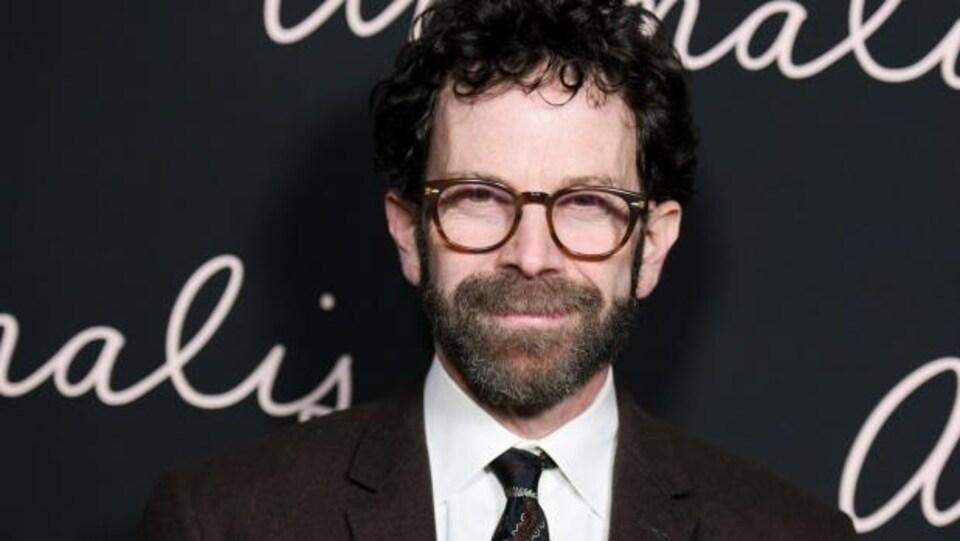 Un homme à la barbe et aux cheveux bruns portant des lunettes.