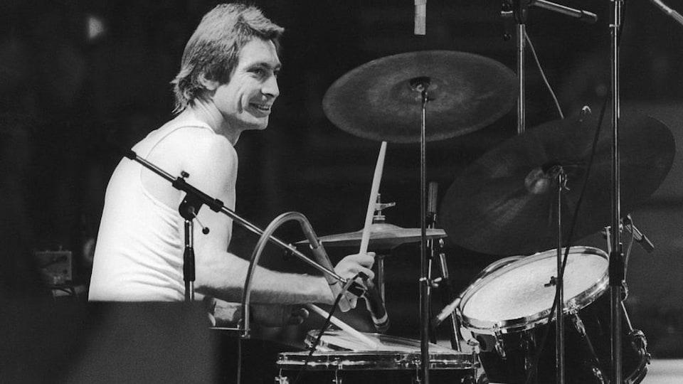 Photo en noir et blanc d'un homme qui joue de la batterie