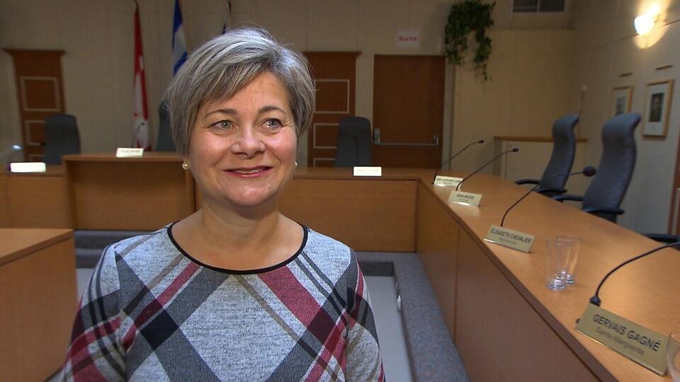 Charlotte Audet, debout dans la salle du conseil municipal de Sept-Îles. Elle sourit à la caméra.