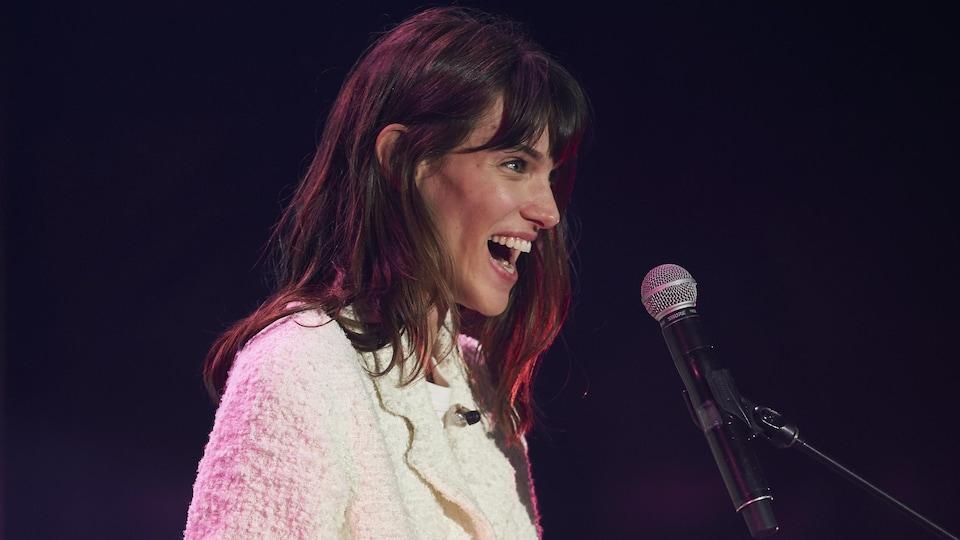 Charlotte Cardin fait un large sourire sur scène.