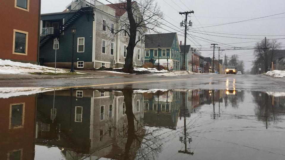 Les maisons se reflètent sur la surface de l'eau qui recouvre une section de la rue.