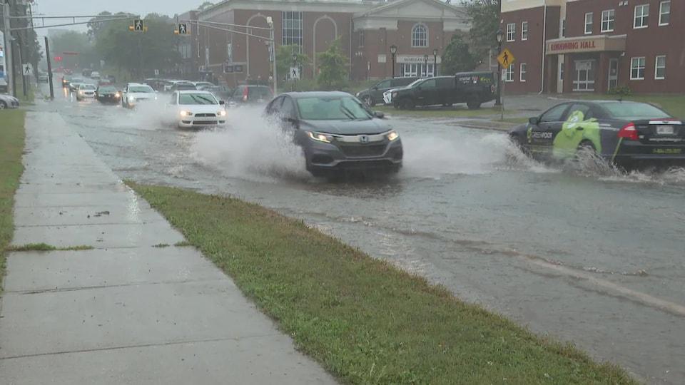 Des voitures dans une rue inondée projettent des gerbes d'eau.