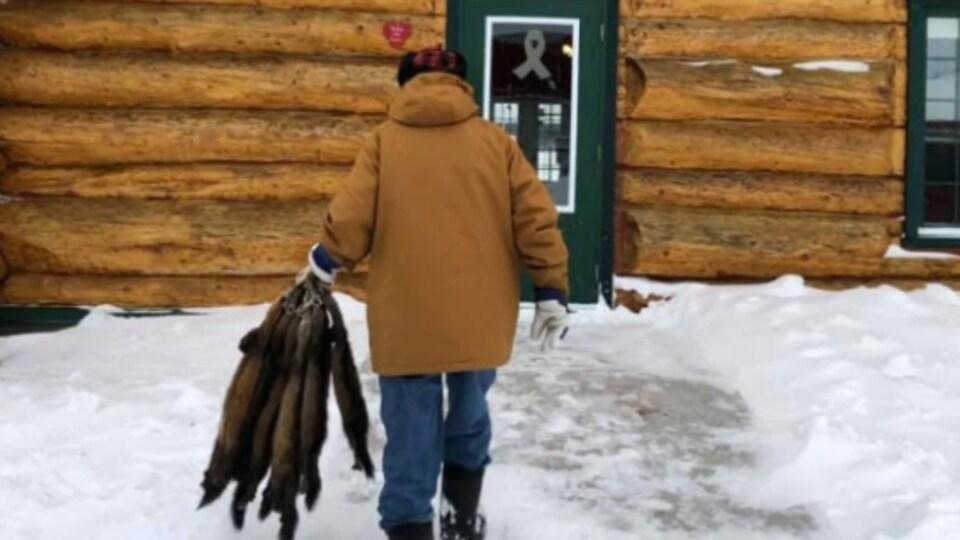 Un homme de dos marche vers une bâtisse en bois avec des peaux de bêtes à la main.