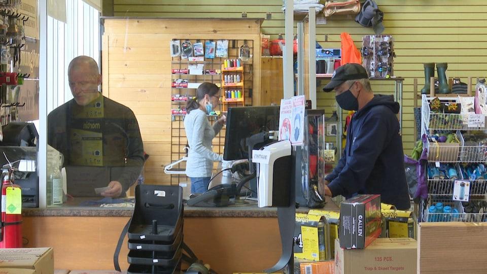 Un client fait un achat à la caisse de la boutique de chasse et pêche.