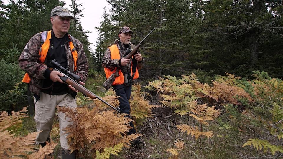 Deux chasseurs marchent en tenant leurs carabines.