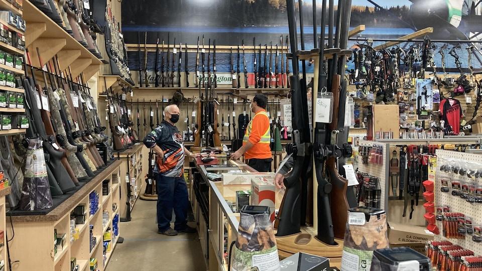 Un client parle à un vendeur dans un magasin de chasse.