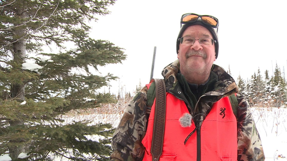 Gilles Couture pose pour la caméra dans un boisé enneigé. Il porte de l'équipement de chasse.