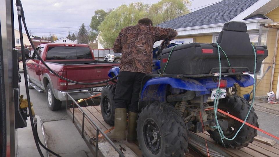 Un homme debout dans une remorque où se trouve un véhicule tout-terrain.