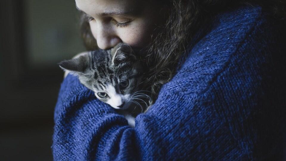 Une adolescente tient un chat dans ses bras.