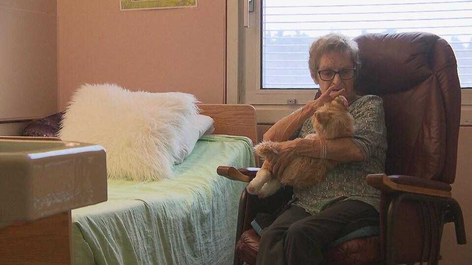 Une femme âgée tient un chat en peluche dans ses bras.