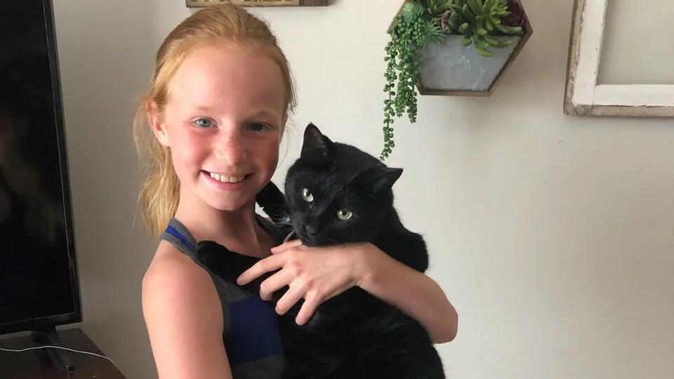 Un chat noir dans les bras d'Alli Urschel.