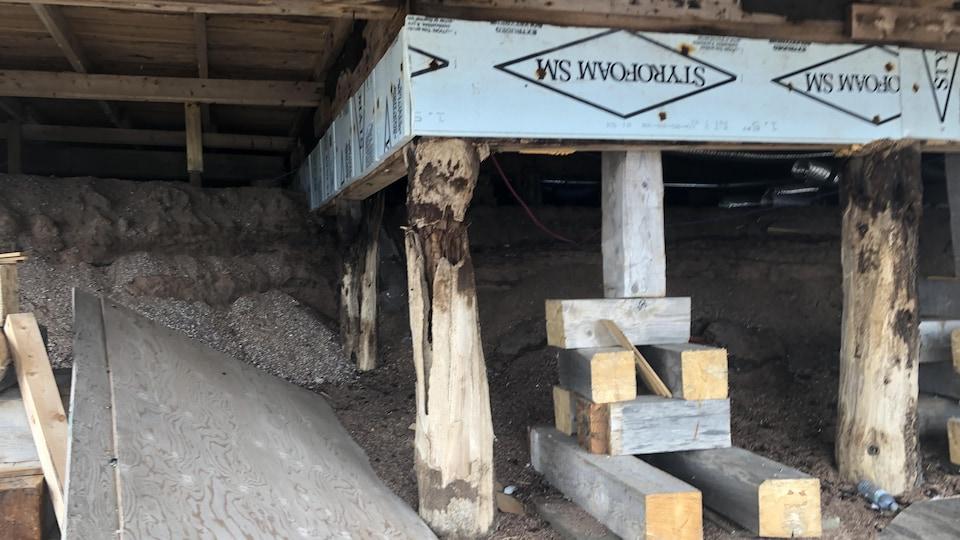 Des poutres qui soutiennent la maison au sous-sol.