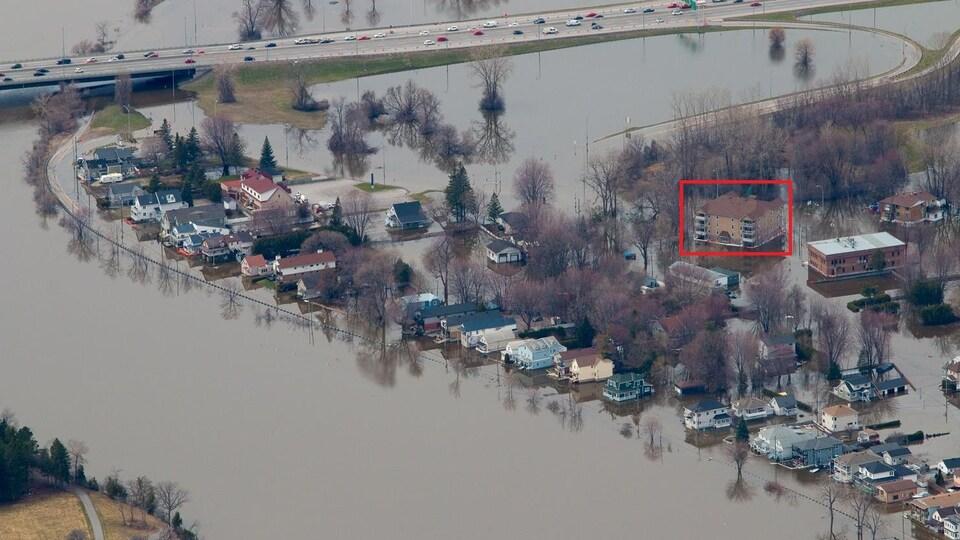 Image aérienne lors des crues printanières, sur laquelle l'immeuble de 16 condominiums, partiellement submergé, est encerclé.