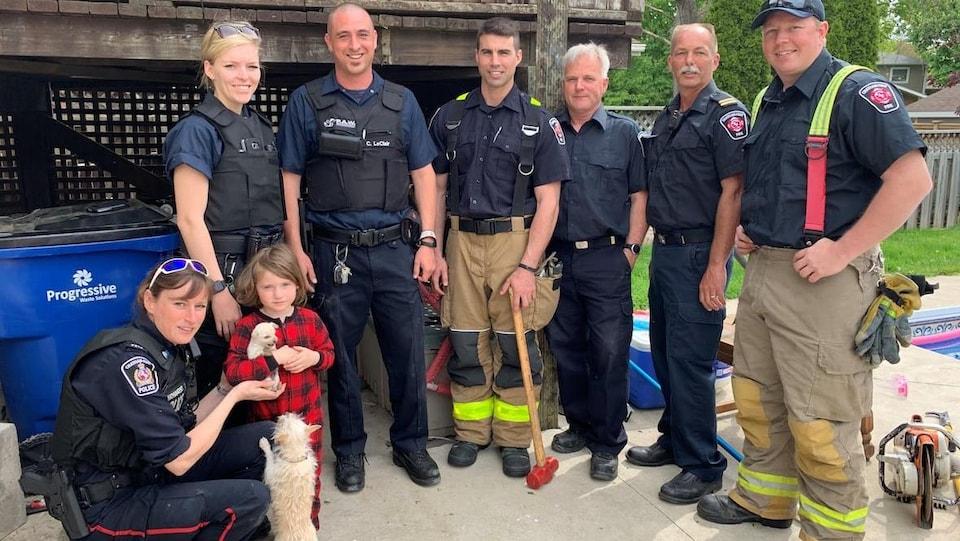 L'équipe de secouristes pose avec le chiot, se réjouissant de cette fin heureuse.