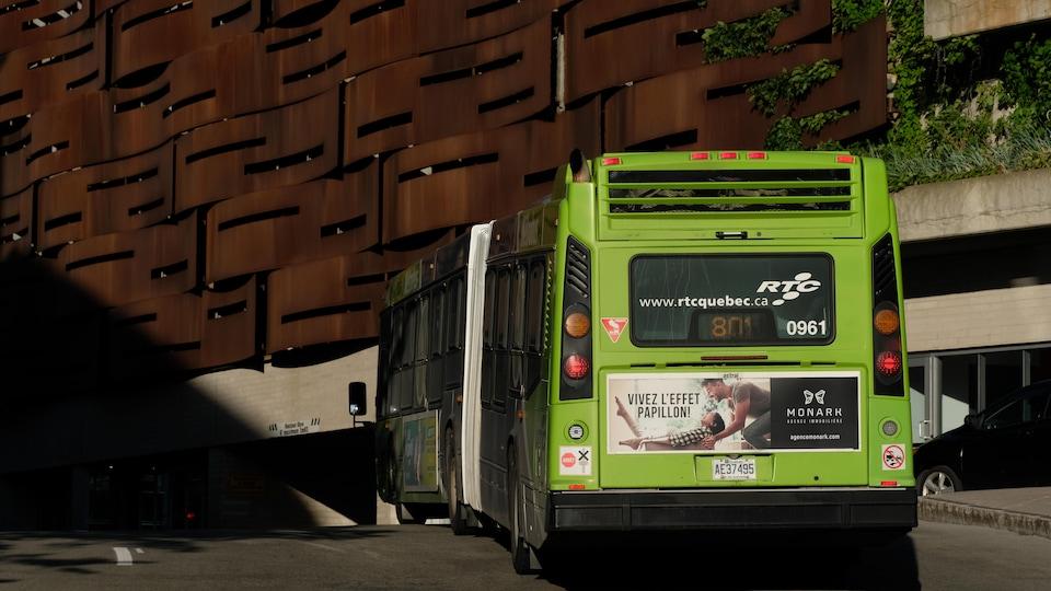 Un autobus circule près d'un bâtiment.