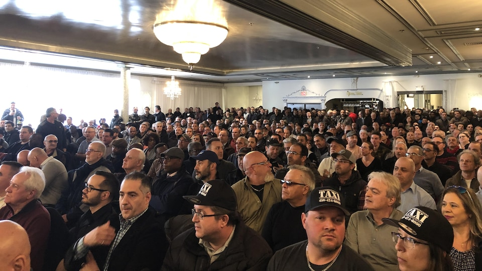 Les chauffeurs de taxi sont réunis dans une grande salle en assemblée générale extraordinaire.