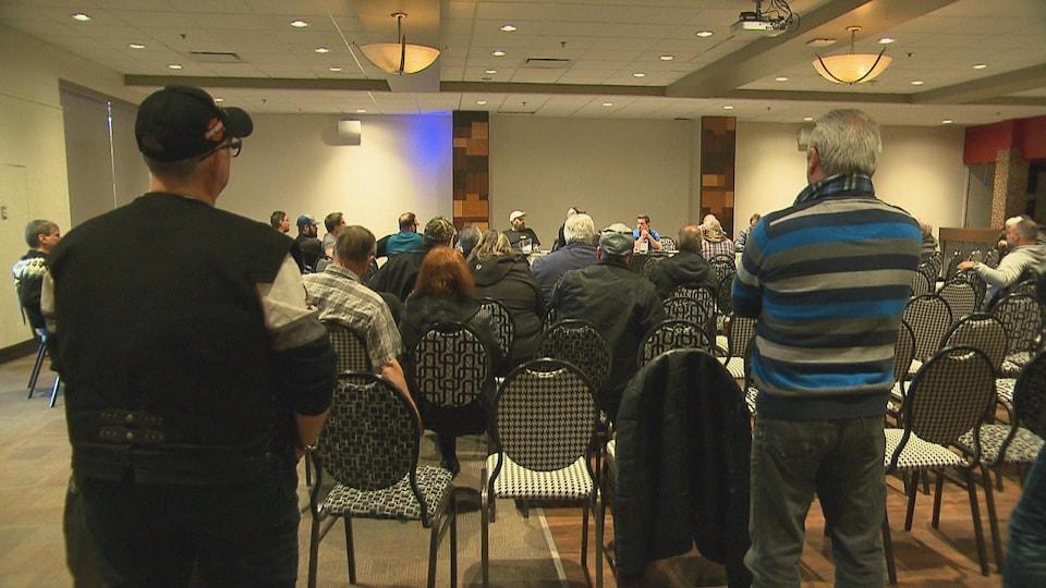Des dizaines de personnes sont assises dans une salle alors que des gens parlent devant.