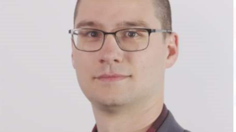 Un homme avec des lunettes pose pour une photo.