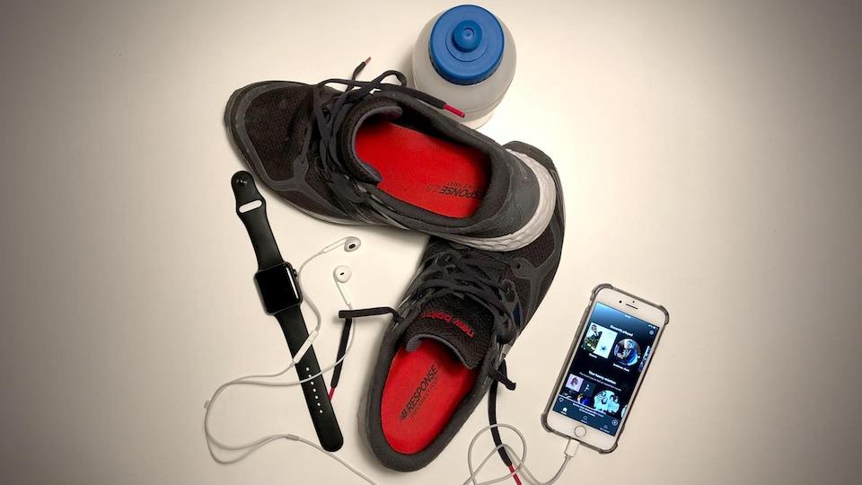 Des souliers de course, un téléphone, une montre et une bouteille d'eau.