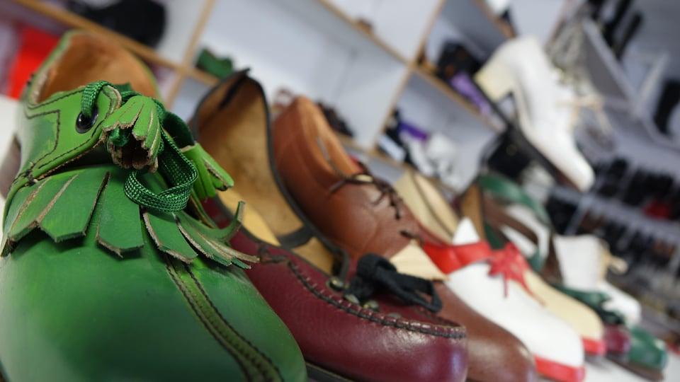 Rangée de chaussures en cuir posées sur un présentoir. Certaines sont vertes, rouges, marron et blanches.