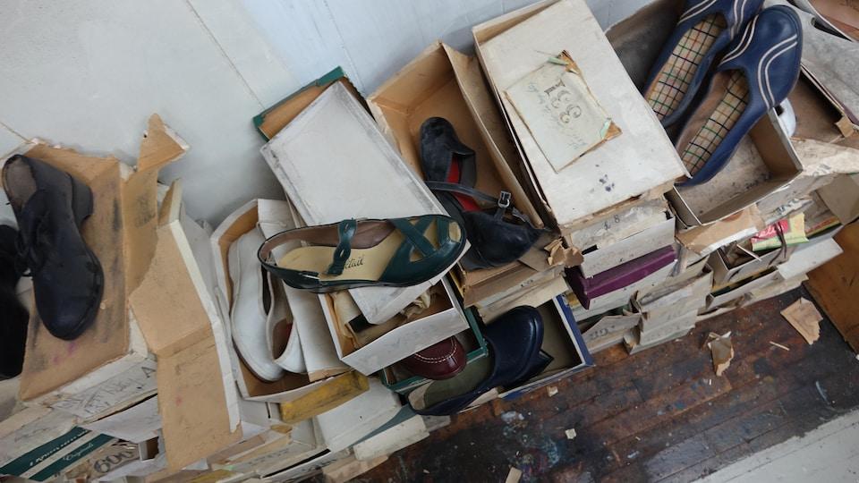 Des piles de vieilles boîtes en carton entassées les unes sur les autres. À l'intérieur de certaines d'entre elles se trouvent des chaussures pour femmes.